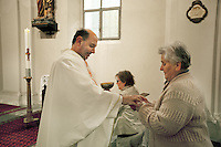 Switzerland. Canton Ticino. Corippo lies in the Verzasca valley. A catholic priest is giving host during the evening mass. With a population of just 16, Corippo is the smallest municipality in Switzerland. Despite this, it possesses the trappings of communities many times its size such as a town council which is a democratically elected form of government for small municipalities. A council may serve as both the representative and executive branch. The village has maintained its status as an independent entity since its incorporation in 1822. A host is a portion of bread used for Holy Communion in many Christian churches. In Western Christianity the host is often a thin, round unleavened wafer. 8.05.13 © 2013 Didier Ruef
