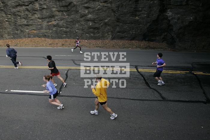 Runners on Kelly Drive look on as men's winner Hosea Kimutal heads to the finish during the Philadelphia Marathon in Philadelphia, Pennsylvania on November 19, 2006.