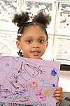 Preschool 4-5 year olds art activity proud girl holding up her drawing recognizable human figures vertical