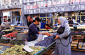 Sarajevo, Bosnia and Herzegovina. Elderly muslim woman with a headscarf paying for goods bought on the market; plums, grapes; peppers.