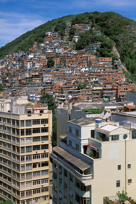 Contrast between middle class buildings in Copacabana in foreground and slum callled favela in Brazil on Morro do Pavao hill , Rio de Janeiro, Brazil