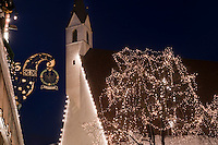 The tree outside the village church has been decorated with fairylights
