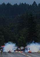 Aug. 6, 2011; Kent, WA, USA; NHRA pro stock driver Greg Anderson (left) does his burnout alongside teammate Jason Line during qualifying for the Northwest Nationals at Pacific Raceways. Mandatory Credit: Mark J. Rebilas-
