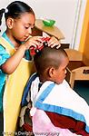 Preschool 3-4 year olds pretend play girl pretending to cut boy's hair using toy fire truck vertical