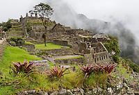Peru, Machu Picchu.  Western Urban Sector.  Huayna Picchu in Clouds in Background.