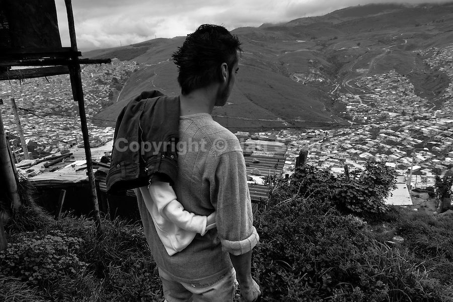 A displaced man stands on the edge of a hill looking out on the valley where slums of Ciudad Bolívar lie, Bogota, Colombia, 27 May 2010. With nearly fifty years of armed conflict, Colombia has the highest number of civil war refugees in the world. During the last ten years of the civil war more than 3 million people have been forced to abandon their lands and to leave their homes due to the violence. Internally displaced people (IDPs) come from remote rural areas, where most of the clashes between leftist guerrillas FARC-ELN, right-wing paramilitary groups and government forces takes place. Displaced persons flee in a hurry, carrying just personal belongings, and thus they inevitably end up in large slums of the big cities, with no hope for the future.