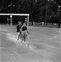 Parc municipal des sports (île du Ramier). 14 septembre 1963. Scène d'inondation : vue de 3/4 face de deux enfants à vélo traversant la zone inondée ; en arrière-plan entrée du Parc municipal des sports envahie par les eaux.