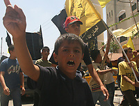 "A Palestinian boy shouts as others carry the body of Hesham al-Jamal, an Islamic Jihad militant who was killed by an Israeli air strike, during his funeral in the southern Gaza Strip August 5, 2007. An Israeli air strike on two vehicles killed two Palestinian militants in the southern Gaza Strip on Saturday, ambulance crews and local residents said.""photo by Fady Adwan"""