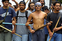 "Unemployed workers known as ""Piqueteros"" carry sticks to confront the police during a demonstration at Plaza de Mayo, in front of the government house Casa Rosada in Buenos Aires, Argentina January 15,2002. Thousands unemployed workers protest today in Buenos Aires against the economic policy that live them without work and food. Photo by Quique Kierszenbaum"