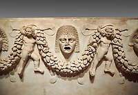 "Close up picture of Roman relief sculpted Sarcophagus of Garlands, 2nd century AD, Perge. This type of sarcophagus is described as a ""Pamphylia Type Sarcophagus"". It is known that these sarcophagi garlanded tombs originated in Perge and manufactured in the sculptural workshops of Perge. Antalya Archaeology Museum, Turkey.. Against a grey background."