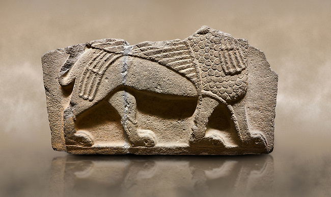 Photo of Hittite monumental relief sculpted orthostat stone panel from Water Gate Basalt, Karkamıs, (Kargamıs), Carchemish (Karkemish), 900-700 B.C. Anatolian Civilisations Museum, Ankara, Turkey.<br /> <br />  A portion of the body and the feet of the Sphinx. Its chest was processed as fish flakes. Parallel lines on its wings draw attention.  <br /> <br /> On a brown art background.