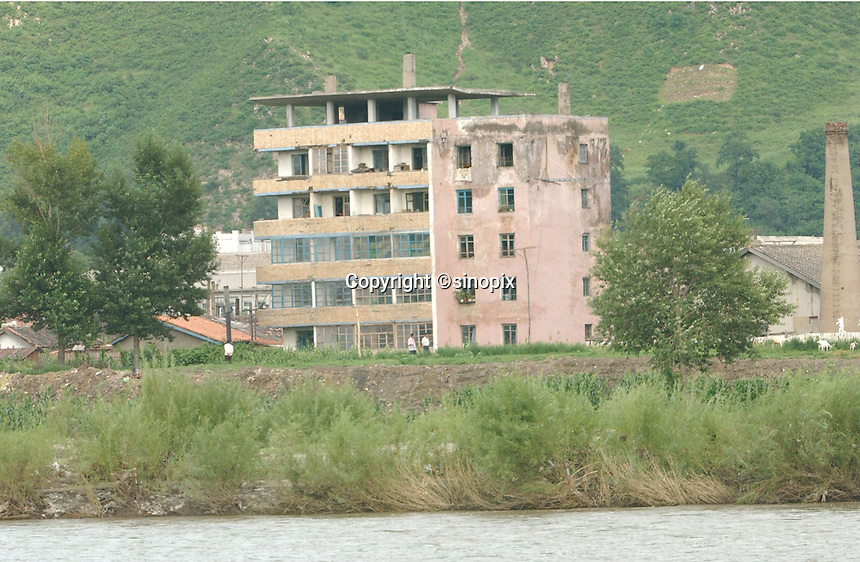 01-AUG-02: NORTH KOREAN BORDER: TUMEN, JILIN, CHINA<br /> The delapidated houses of the North Korean border town as seen from the Chinese border town of Tumen, on the Tumen River. The Tumen River is just 20 meters wide and often crossed by North Koreans fleeing famine and oppression.