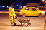 10/10/2014 -- Kirkuk, Iraq -- A Bangladeshi worker cleans the street at night in the Iskan neighborhood.