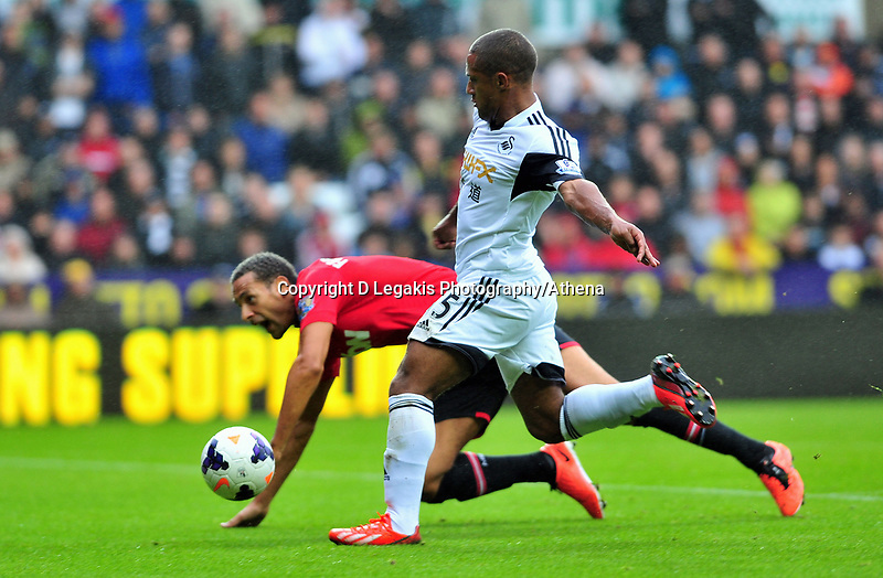 Swansea's Wayne Routledge takes a shot on goal after getting passed Rio Ferdinand.<br /> Saturday 17 August 2013<br /> Pictured: <br /> Re: Barclays Premier League Swansea City v Manchester United at the Liberty Stadium, Swansea, Wales