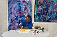 Leroy Exil, artist, with his artwork, painting at his home.