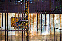 An empty concrete cage with rusted bars in the monkey area of the Havana Zoo, Havana, Cuba, 12 February 2011. The largest and the oldest zoo in Cuba (founded in 1939) is located in a centric neighborhood of the capital. Since the 1990s Cuba struggles with chronic economic crisis and therefore the strong marks of rundown and lack of sources are evident within the whole zoological garden. A lot of cages are empty and out of use for long time, the remaining animals are captured in poorly maintained pits. Concrete enclosures have no vegetation, all facilities are unkept. The food supply is often inadequate and visitors throw junkfood to the animals because there are no zookeepers around.