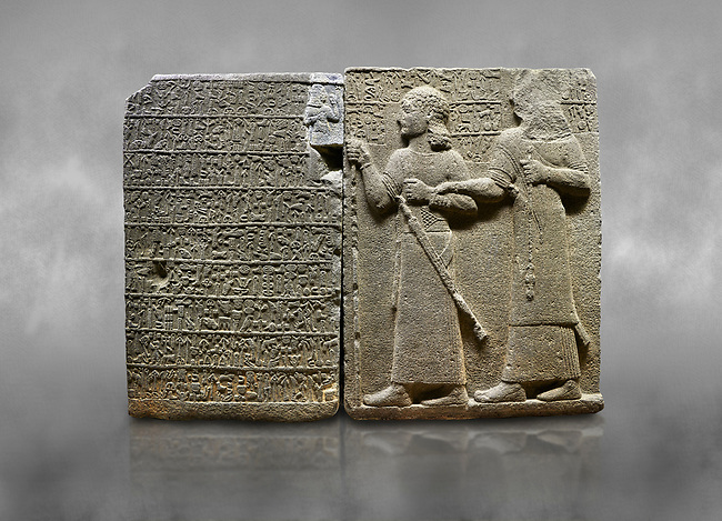 "Hittite monumental relief sculpted orthostat stone panel of Royal Buttress. Basalt, Karkamıs, (Kargamıs), Carchemish (Karkemish), 900-700 B.C. Anatolian Civilisations Museum, Ankara, Turkey.<br /> <br /> Hieroglyph panel (left) - Discourse of Yariris. Yariris presents his predecessor, the eldest son Kamanis, to his people. <br /> Right Panel - King Araras holds his son Kamanis from the wrist. King carries a sceptre in his hand and a sword at his waist while the prince leans on a stick and carries a sword on his shoulder. <br /> <br /> Hieroglyphs reads; ""This is Kamanis and his siblings. held his hand and despite the fact that he is a child, I located him on the temple. This is Yariris' image"".  <br /> <br /> Against a grey art background."