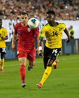 NASHVILLE, TN - JULY 3: Shaun Francis #14 and Jordan Morris #11 charge to the ball during a game between Jamaica and USMNT at Nissan Stadium on July 3, 2019 in Nashville, Tennessee.