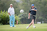 Robbie Fowler (right) kicks a football while John Daly watches during the World Celebrity Pro-Am 2016 Mission Hills China Golf Tournament on 23 October 2016, in Haikou, Hainan province, China. Photo by Weixiang Lim / Power Sport Images