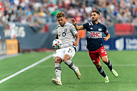 FOXBOROUGH, MA - JULY 25: Zorhan Bassong #19 of CF Montreal clears the ball as Carles Gil #22 of New England Revolution defends during a game between CF Montreal and New England Revolution at Gillette Stadium on July 25, 2021 in Foxborough, Massachusetts.