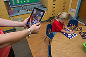 MR / Schenectady, NY. Zoller Elementary School (urban public school). Kindergarten inclusion classroom. Teacher uses iPad to photograph student (girl, 5) using templates to draw shapes during math learning center time. Photographs of students working are used by teachers to chart progress and evaluate skills of their students. MR: Deg9. ID: AM-gKw. © Ellen B. Senisi.