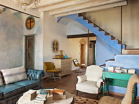 The walls of the living room and entrance have been painted with tinted limewash, layered to create an aged effect and the staircase a pastel blue
