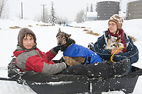 Dropped dog volunteers take a couple dropped dogs to the airport at McGrath during Iditarod 2009