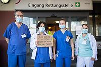 """Corona-Krise - Alltagsheldinnen und Helden.<br /> Im Bild: Medizinisches Personal des Urban-Krankenhaus in Berlin-Kreuzberg mit einem Schild """"WIR BLEIBEN fuer euch da!! BLEIBT ihr bitte fuer uns DAHEIM"""".<br /> 25.3.2020, Berlin<br /> Copyright: Christian-Ditsch.de<br /> [NUR FUER REDAKTIONELLE ZWECKE! Werbung nur auf Anfrage beim Fotografen. Inhaltsveraendernde Manipulation des Fotos nur nach ausdruecklicher Genehmigung des Fotografen. Vereinbarungen ueber Abtretung von Persoenlichkeitsrechten/Model Release der abgebildeten Person/Personen liegen nicht vor. NO MODEL RELEASE! Don't publish without copyright Christian-Ditsch.de, Veroeffentlichung nur mit Fotografennennung, sowie gegen Honorar, MwSt. und Beleg. Konto: I N G - D i B a, IBAN DE58500105175400192269, BIC INGDDEFFXXX, Kontakt: post@christian-ditsch.de<br /> Bei der Bearbeitung der Dateiinformationen darf die Urheberkennzeichnung in den EXIF- und  IPTC-Daten nicht entfernt werden, diese sind in digitalen Medien nach §95c UrhG rechtlich geschuetzt. Der Urhebervermerk wird gemaess §13 UrhG verlangt.]"""