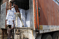 Men unload boxes from the back of a lorry in central Kolkata.<br />