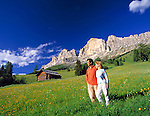 Italy, South Tyrol, Alto Adige, Dolomites,  couple in flower meadow and Cima Catinaccio mountain range (2.981 m)