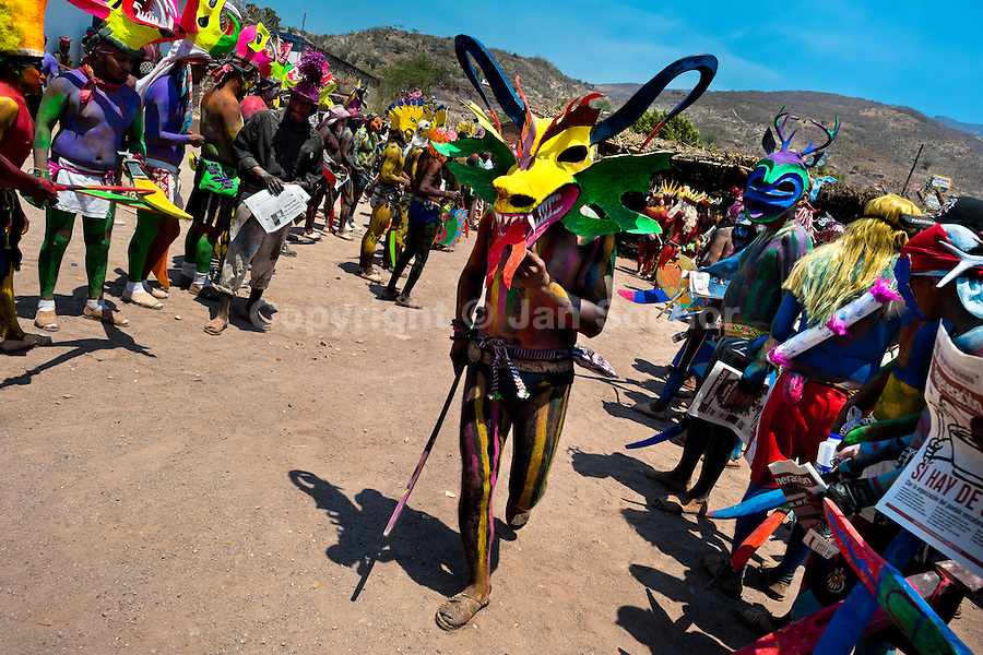 """A Cora Indian man, wearing a scary colorful demon mask, walks in a procession during the sacred ritual ceremony of Semana Santa (Holy Week) in Jesús María, Nayarit, Mexico, 22 April 2011. The annual week-long Easter festivity (called """"La Judea""""), performed in the rugged mountain country of Sierra del Nayar, merges indigenous tradition (agricultural cycle and the regeneration of life worshipping) and animistic beliefs with the Christian dogma. Each year in the spring, the Cora villages are taken over by hundreds of wildly running men. Painted all over their semi-naked bodies, fighting ritual battles with wooden swords and dancing crazily, they perform demons (the evil) that metaphorically chase Jesus Christ, kill him, but finally fail due to his resurrection. La Judea, the Holy Week sacred spectacle, represents the most truthful expression of the Coras' culture, religiosity and identity."""