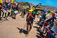 "A Cora Indian man, wearing a scary colorful demon mask, walks in a procession during the sacred ritual ceremony of Semana Santa (Holy Week) in Jesús María, Nayarit, Mexico, 22 April 2011. The annual week-long Easter festivity (called ""La Judea""), performed in the rugged mountain country of Sierra del Nayar, merges indigenous tradition (agricultural cycle and the regeneration of life worshipping) and animistic beliefs with the Christian dogma. Each year in the spring, the Cora villages are taken over by hundreds of wildly running men. Painted all over their semi-naked bodies, fighting ritual battles with wooden swords and dancing crazily, they perform demons (the evil) that metaphorically chase Jesus Christ, kill him, but finally fail due to his resurrection. La Judea, the Holy Week sacred spectacle, represents the most truthful expression of the Coras' culture, religiosity and identity."