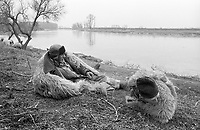 ROMANIA, 04.1981, Oltenita pond, along the Danube..Shepherds wrapped in their sheepskin coasts on the banks of the pond in Oltenita..ROUMANIE, 04.1981, étang d'Oltenitza, en bordure du Danube..Bergers emmitouflés dans leurs manteaux de peaux de moutons sur les rives de l'étang d'Oltetiza..© Andrei Pandele / Est&Ost Photography..