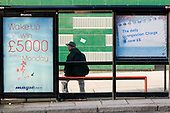 A teenage boy waits at a bus stop displaying a Congestion Charge poster on the Harrow Road, West London.