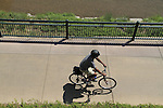 Black man riding his bike on a sidewalk in Denver, Colorado. .  John offers private photo tours in Denver, Boulder and throughout Colorado. Year-round.