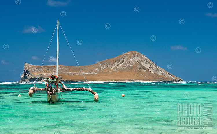 An outrigger sailboat in front of Manana Island, a.k.a. Rabbit Island, on the Windward side of O'ahu.