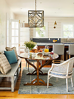 The spacious kitchen dining area has painted wood panelling on the walls and a wood floor. An island unit provides a central cooking area and doubles as a breakfast bar. The dining area  is furnished with a traditional wood oval dining table and the dining chairs are of painted wicker. A bench seat is against one wall and there is a grey rug on the floor. A square lantern style pendant light hangs above the table.