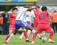 Patrick Viera (4) of France is hemmed in by Eul Yong Lee (13) and Young Chul Kim (2) of Korea. The Korea Republic and France played to a 1-1 tie in their FIFA World Cup Group G match at the Zentralstadion, Leipzig, Germany, June 18, 2006.
