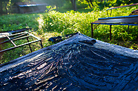 The indigo paste, spread out on a metal sheet table, is seen drying in the sun at the semi-industrial manufacture near San Miguel, El Salvador, 12 November 2016. For centuries, indigo, a natural deep blue dye extracted from the leaves of tropical plants (Indigofera), has been known to the native indigenous inhabitants of Central America who used the blue tincture to color their fabrics and pottery. Although demand for natural indigo dropped significantly at the end of 19th century when a synthetic indigo was firstly introduced, commercialization of natural indigo has risen again during the last decades. Small-scale indigo farms, processing the crop on sustainable and ecological basis, are growing throughout the country, returning El Salvador to the place of the main natural indigo producer in Latin America.