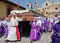 Antigua, Guatemala.  Adolescent Boys Carrying a Float in a Religious Procession during Holy Week, La Semana Santa.  La Merced Church in Background.