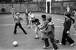 School boys playing football in junior school playground lunch break South London England 1970s...