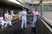 Second baseman Yoan Moncada of the Greenville Drive looks out from the dugout in the second game of his pro career against the Lexington Legends on Tuesday, May 19, 2015, at Fluor Field at the West End in Greenville, South Carolina. The Cuban-born 19-year-old Red Sox signee has been ranked the No. 1 international prospect in baseball by Baseball America. (Tom Priddy/Four Seam Images)