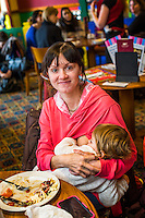 Portrait of a mother breastfeeding her child while sitting at a table during  a sling meet held in the family restaurant and play area in a pub.<br /> Lancashire, England, UK<br /> <br /> Date Taken:<br /> 07-01-2015<br /> <br /> © Paul Carter / wdiip.co.uk