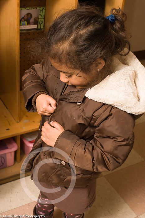 Education Preschool 3-4 year olds fine motor skills girl zipping coat vertical