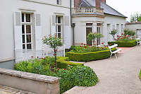The Deutz building seen from the garden behind the main house with red roses and sculptured bushes at Champagne Deutz in Ay, Vallee de la Marne, Champagne, Marne, Ardennes, France