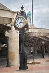 A clock stands on a street.
