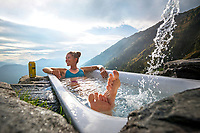 Soaking in the Capanna Nimi's bath tub in the evening while hiking the Via Alta Val Maggia, a week long, difficult trek connecting Locarno and Broglio that stays high on a remote and wild ridgeline. Switzerland.