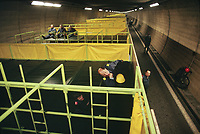 Switzerland. Canton Lucerne. People lying on bunk beds in the Sonnenberg tunnel in Lucerne during the largest civil defense exercise ever held in the country. From 16 to 21 November 1987, almost 1200 men and women converted a motorway tunnel into perhaps the world's largest bunker structure. The civil protectors had to prove during the exercise «Ameise » ( Ants in english) that in an emergency more than 20,000 inhabitants of the city of Lucerne could survive here in the mountain for two weeks. The Sonnenberg Tunnel is a 1,550 m  long motorway tunnel, constructed between 1971 and 1976. At its completion it was also the world's largest civilian nuclear fallout shelter, designed to protect 20,000 civilians in the eventuality of war or disaster. Based on a federal law from 1963, Switzerland aims to provide nuclear fallout shelters for the entire population of the country. The construction of a new tunnel near an urban centre was seen as an opportunity to provide shelter space for a large number of people at the same time. The giant bunker was built between 1970 and 1976 at a cost of 40 million Swiss francs. The shelter consisted of the two motorway tunnels (one per direction of travel), each capable of holding 10,000 people in 64 person subdivisions. A seven story cavern between the tunnels contained shelter infrastructure including a command post, an emergency hospital, a radio studio, a telephone centre, prison cells and ventilation machines. The shelter was designed to withstand the blast from a 1 megaton nuclear explosion 1 kilometer away. The blast doors at the tunnel portals are 1.5 meters thick and weigh 350 tons. The logistical problems of maintaining a population of 20,000 in close confines were not thoroughly explored, and testing the installation was difficult because it required closing the motorway and rerouting the usual traffic. The only large-scale test, a five-day exercise in 1987 to practice converting the road tunnels into usable shelters, reveale