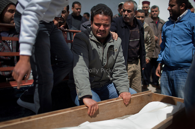 A man wept next to a coffin carrying a dead body at the hospital morgue in Benghazi, Libya, March 20, 2011. Family members prepared those killed during fighting between opposition rebels and loyalist forces of Col. Muammar Qaddafi for burial. The main hospital in Benghazi reported around 50 dead fighters and civilians the previous day and at least 35 on Sunday.