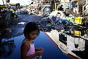 A young girl walks past though a shanty town with an alley filled with collected rain water in Sitio Aroma in Barangay 105, Manila in Philippines. Photo: Sanjit Das